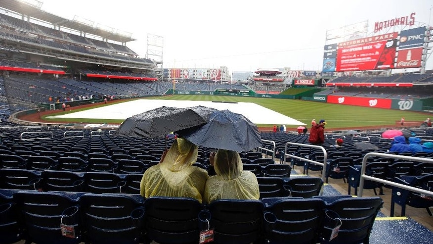 Fans sit under umbrellas in the rain before an exhibition baseball game between the Washington Nationals and the Detroit Tigers at Nationals Park Saturday, March 29, 2014, in Washington. The game was canceled due to weather. (AP Photo/Alex Brandon)