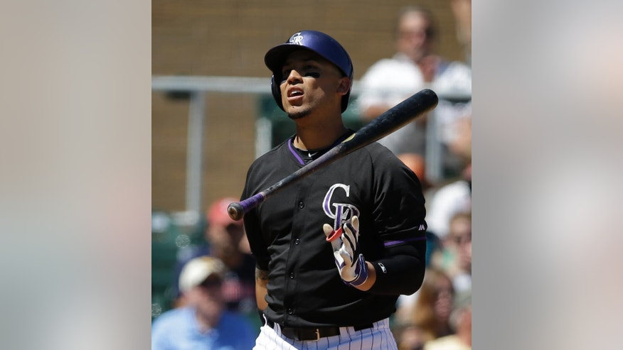 Colorado Rockies' Carlos Gonzalez tosses his bat after striking out during the third inning of an exhibition baseball game against the Seattle Mariners on Saturday, March 29, 2014, in Scottsdale, Ariz. (AP Photo/Darron Cummings)