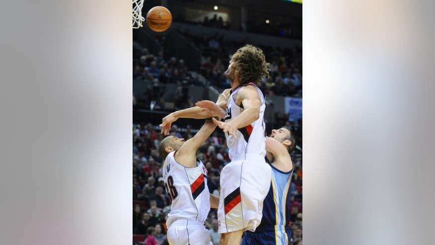 Memphis Grizzlies' Kosta Koufos (41) has his shot blocked by Portland Trail Blazers' Robin Lopez (42) with Nicolas Batum (88) during the first half of an NBA basketball game in Portland, Ore., Sunday March 30, 2014. (AP Photo/Greg Wahl-Stephens)