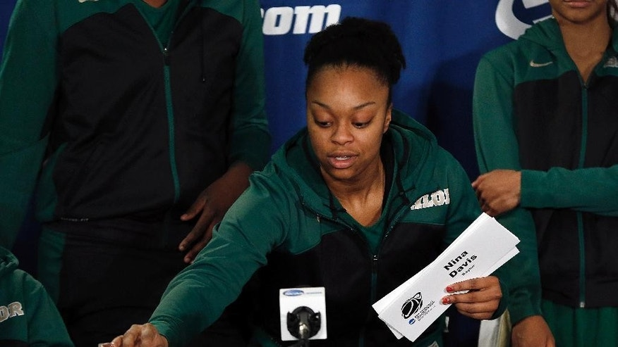 Baylor guard Odyssey Sims places a name plate for teammate Sune Agbuke, spelled incorrectly on the card, before a news conference, Sunday, March 30, 2014 to talk about their NCAA women's college basketball tournament regional final game against Notre Dame on Monday at the Purcell Pavilion in South Bend, Ind. (AP Photo/Paul Sancya)