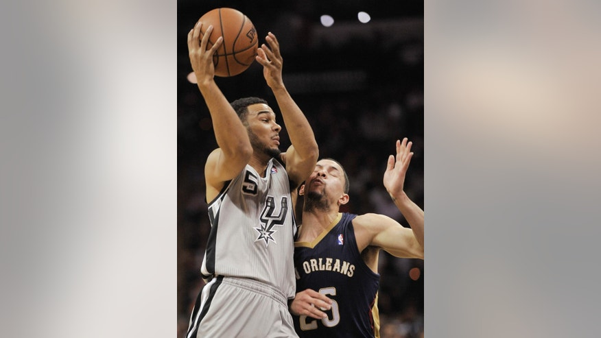 San Antonio Spurs guard Cory Joseph, left, collides with New Orleans Pelicans guard Austin Rivers during the first half of an NBA basketball game on Saturday, March 29, 2014, in San Antonio. (AP Photo/Darren Abate)