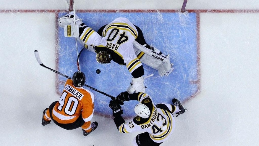 Philadelphia Flyers' Vincent Lecavalier, left, tries to shoot past Boston Bruins' Tuukka Rask, top, of Finland, and Matt Bartkowski (43) during the second period of an NHL hockey game on Sunday, March 30, 2014, in Philadelphia. (AP Photo/Matt Slocum)