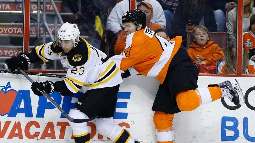 Philadelphia Flyers' Kimmo Timonen right, of Finland, skates into Boston Bruins' Chris Kelly during the first period of an NHL hockey game on Sunday, March 30, 2014, in Philadelphia. (AP Photo/Matt Slocum)