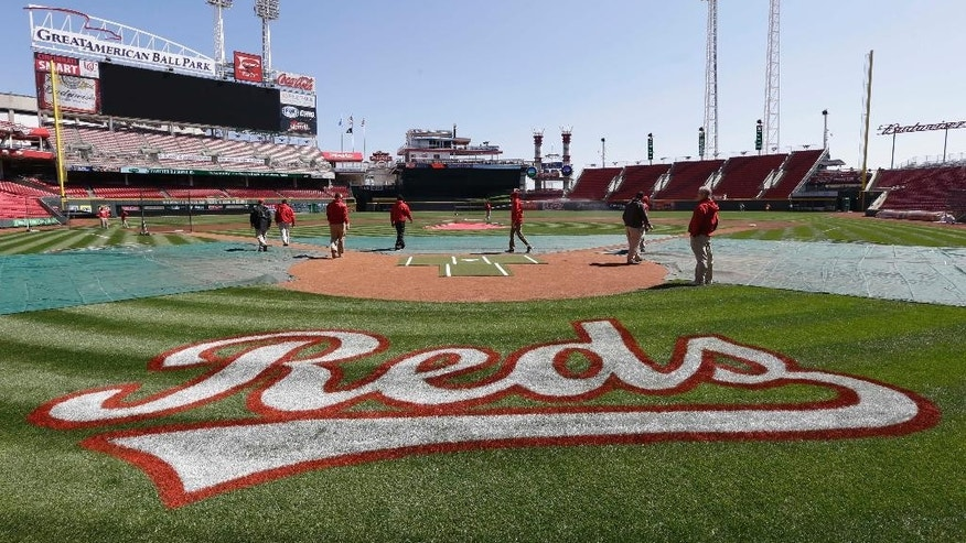 The Cincinnati Reds grounds crew checks the field on Sunday, March 30, 2014, in Cincinnati. The Reds host the St. Louis Cardinals, Monday afternoon in their Opening Day baseball game. (AP Photo/Al Behrman)