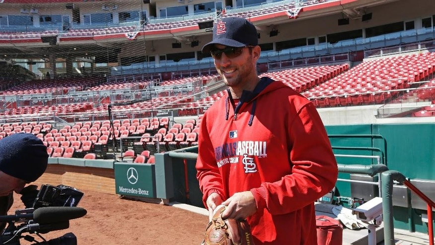 St. Louis Cardinals starting pitcher Adam Wainwright walks onto the field at the start of batting practice on Sunday, March 30, 2014, in Cincinnati. Wainwright will be the starting pitcher for the Cardinals in Monday's Opening Day baseball game against the Cincinnati Reds in Cincinnati. (AP Photo/Al Behrman)