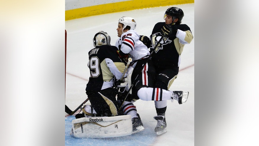 Chicago Blackhawks' Andrew Shaw, center, collides with Pittsburgh Penguins goalie Marc-Andre Fleury (29) and Matt Niskanen, right, in the first period of an NHL hockey game in Pittsburgh, Sunday, March 30, 2014. (AP Photo/Gene J. Puskar)