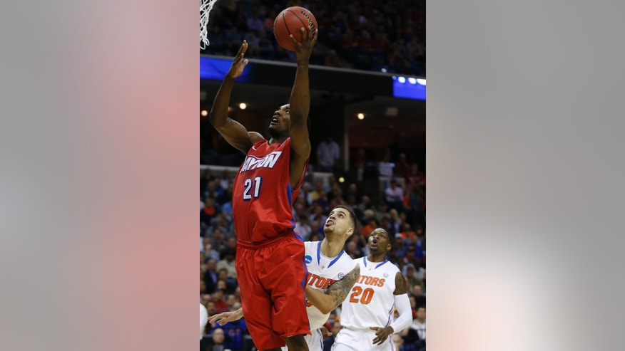 Dayton forward Dyshawn Pierre (21) shoots by Florida guard Scottie Wilbekin (5) and Florida guard Michael Frazier II (20) during the first half in a regional final game at the NCAA college basketball tournament, Saturday, March 29, 2014, in Memphis, Tenn. (AP Photo/John Bazemore)