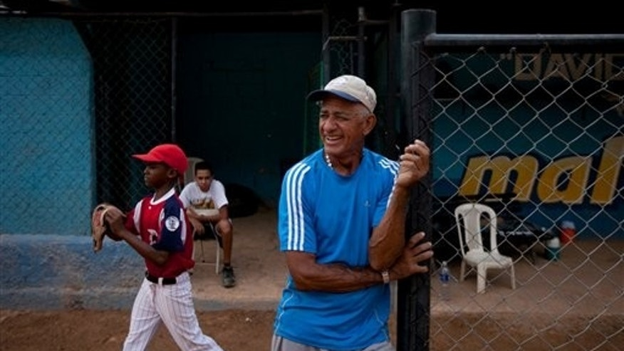 The uncle of Detroit Tigers' Miguel Cabrera, Jose Torres, watches a practice at the baseball field where Cabrera learned to play, in Maracay, Venezuela, Friday, March 28, 2014. Unlike many Latin American countries, where soccer is king, baseball is the national obsession in Venezuela, cutting across classes and political ideologies. Cabrera was born into a family particularly wrapped up in the sport. His uncle Jose played professionally with the local Tigres de Aragua team, and his mother Gregoria was a member of the national softball team for 12 years. (AP Photo/Alejandro Cegarra)