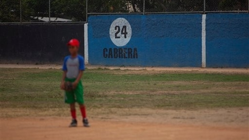 A boy waits for a ball during a fielding and batting practice in the hometown of Detroit Tiger's Miguel Cabrera, in Maracay, Venezuela, Friday, March 28, 2014. Cabrera, 30, learned to play on this same field, now remodeled thanks to his economic support. On Friday, he signed the richest contract in baseball history, a $292 million 10-year deal with the Tigers. The number painted on the back wall is Cabrera's jersey number. (AP Photo/Alejandro Cegarra)