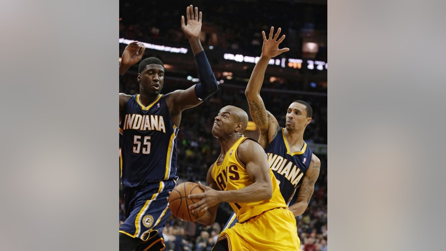 Cleveland Cavaliers' Jarrett Jack, front, drives by Indiana Pacers' Roy Hibbert, left, and George Hill, right, during the second quarter of an NBA basketball game Sunday, March 30, 2014, in Cleveland. (AP Photo/Tony Dejak)