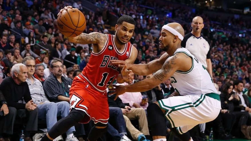 Chicago Bulls' D.J. Augustin (14) drives past Boston Celtics' Jerryd Bayless in the second quarter of an NBA basketball game in Boston, Sunday, March 30, 2014. (AP Photo/Michael Dwyer)