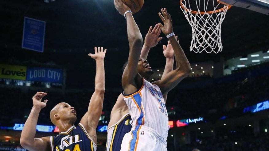 Oklahoma City Thunder forward Kevin Durant (35) shoots in front of Utah Jazz forward Richard Jefferson (24) in the second quarter of an NBA basketball game in Oklahoma City, Sunday, March 30, 2014. (AP Photo/Sue Ogrocki)
