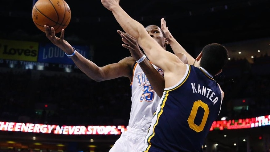 Oklahoma City Thunder forward Kevin Durant (35) shoots as Utah Jazz center Enes Kanter (0) defends in the first quarter of an NBA basketball game in Oklahoma City, Sunday, March 30, 2014. (AP Photo/Sue Ogrocki)