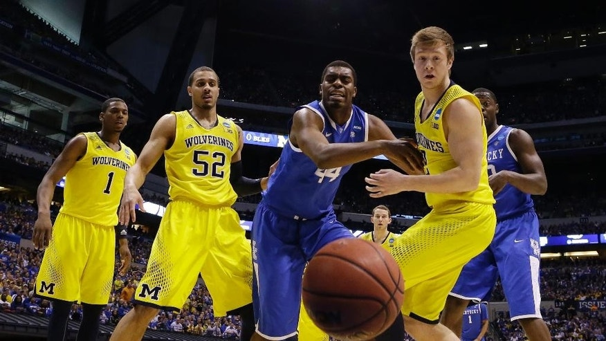 Kentucky's Dakari Johnson (44) and Michigan's Spike Albrecht (2) go after a loose ball as Michigan's Glenn Robinson III (1) and Jordan Morgan (52) watch during the first half of an NCAA Midwest Regional final college basketball tournament game Sunday, March 30, 2014, in Indianapolis. (AP Photo/Michael Conroy)