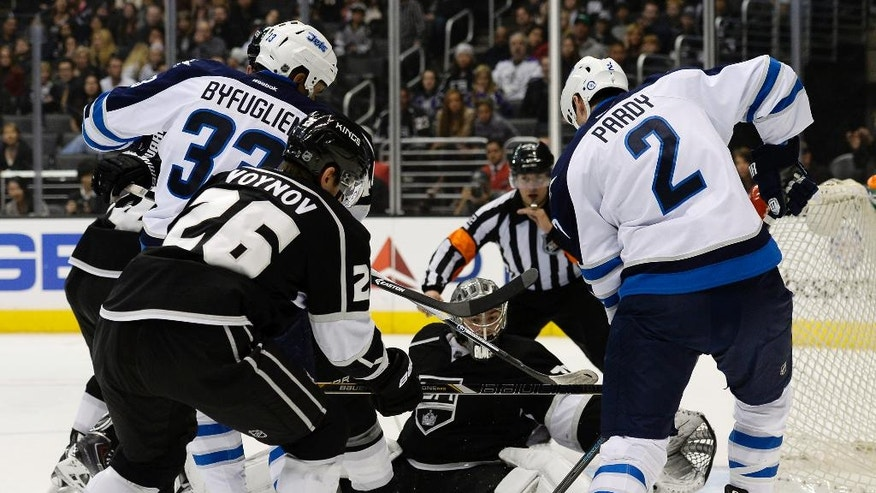 Los Angeles Kings goalie Jonathan Quick blocks a shoot on goal by Winnipeg Jets defenseman Adam Pardy, right, during the first period of an NHL hockey game Saturday, March 29, 2014, in Los Angeles. (AP Photo/Kevork Djansezian)