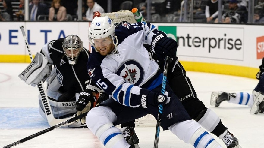 Winnipeg Jets right wing Matt Halischuk goes around Los Angeles Kings goalie Jonathan Quick, railing a defender during the first period of an NHL hockey game Saturday, March 29, 2014, in Los Angeles. (AP Photo/Kevork Djansezian)