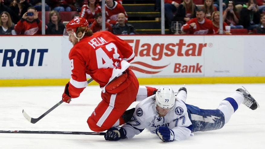 Tampa Bay Lightning's Victor Hedman (77), of Sweden, trips Detroit Red Wings' Darren Helm (43) after knocking away the puck as Helm skated toward the goal during the second period of an NHL hockey game on Sunday, March 30, 2014, in Detroit. (AP Photo/Duane Burleson)
