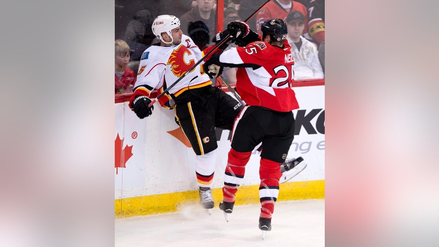 Ottawa Senators winger Chris Neil, right, sends Calgary Flames defenseman Mark Giordano into the boards during the first period of an NHL hockey game, Sunday, March 30, 2014, in Ottawa. (AP Photo/The Canadian Press, Adrian Wyld)