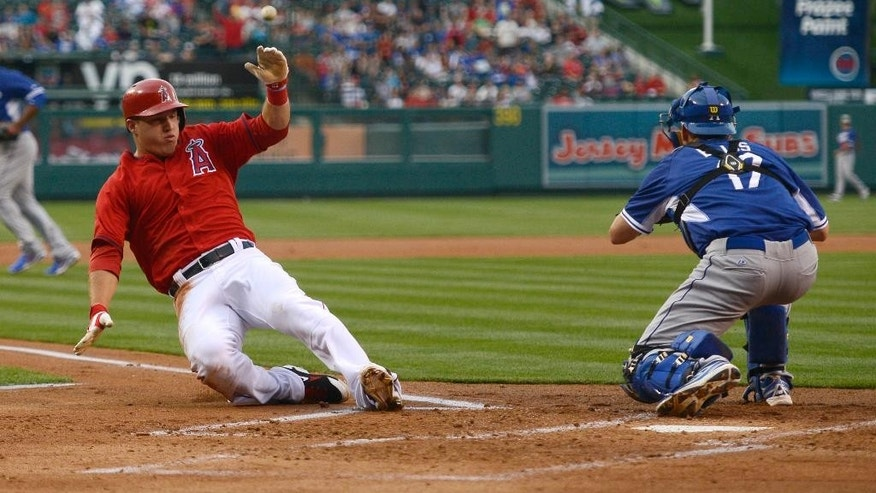 Los Angeles Angels' Mike Trout, left, slides in for a score in front of Los Angeles Dodgers catcher A.J. Ellis  during the first inning of an exhibition baseball game in Anaheim, Calif., Saturday, March 29, 2014. (AP Photo/Kelvin Kuo)