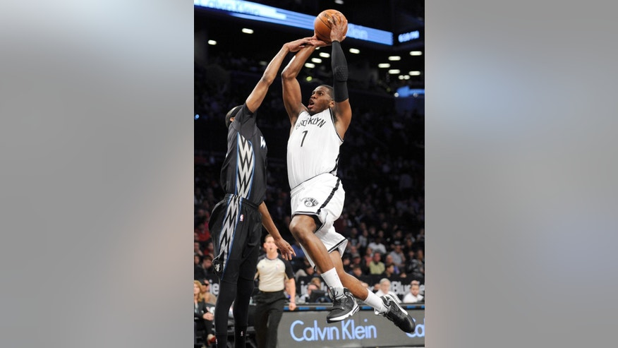 Brooklyn Nets' Joe Johnson (7) is fouled by Minnesota Timberwolves' Corey Brewer while driving to the basket during the first quarter of an NBA basketball game on Sunday, March 30, 2014, at Barclay's Center in New York. (AP Photo/Bill Kostroun)