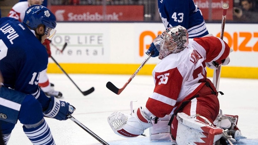 Detroit Red Wings goaltender Jimmy Howard makes a save on Toronto Maple Leafs left winger Joffrey Lupul during second-period NHL hockey game action in Toronto, Saturday, March 29, 2014. (AP Photo/The Canadian Press, Frank Gunn)
