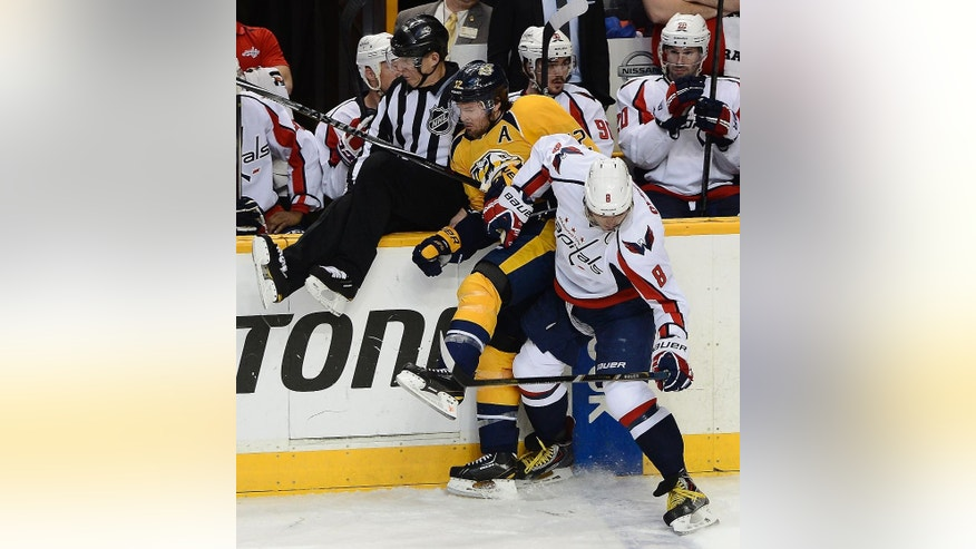 Washington Capitals right wing Alex Ovechkin (8), of Russia, checks Nashville Predators forward Mike Fisher (12) into the boards as linesman Brad Lazarowich, left, tries to get out of the way in the second period of an NHL hockey game on Sunday, March 30, 2014, in Nashville, Tenn.  (AP Photo/Mark Zaleski)