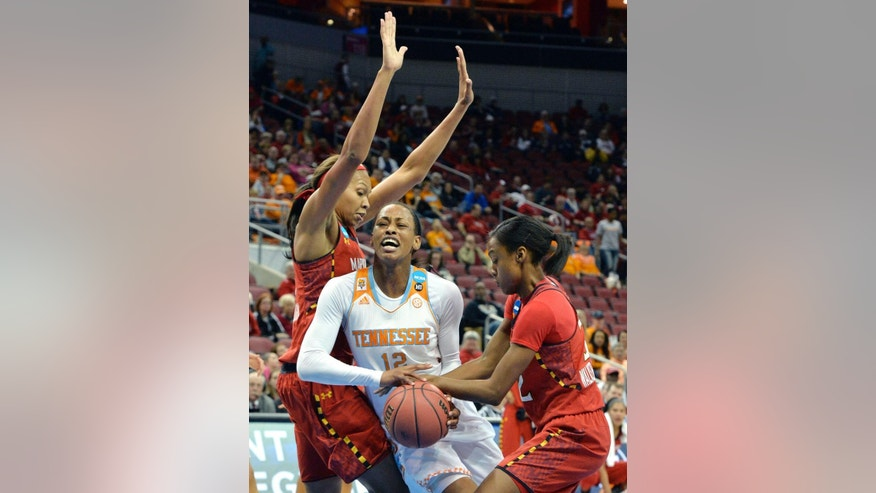 Tennessee's Bashaara Givens, center, fights her way through the defense of Maryland's Alicia Devaughn, left, and Shatori Walker Kimbrough during the first half in a regional semifinal game at the NCAA women's college basketball tournament, Sunday, March 30, 2014, in Louisville, Ky. (AP Photo/Timothy D. Easley)