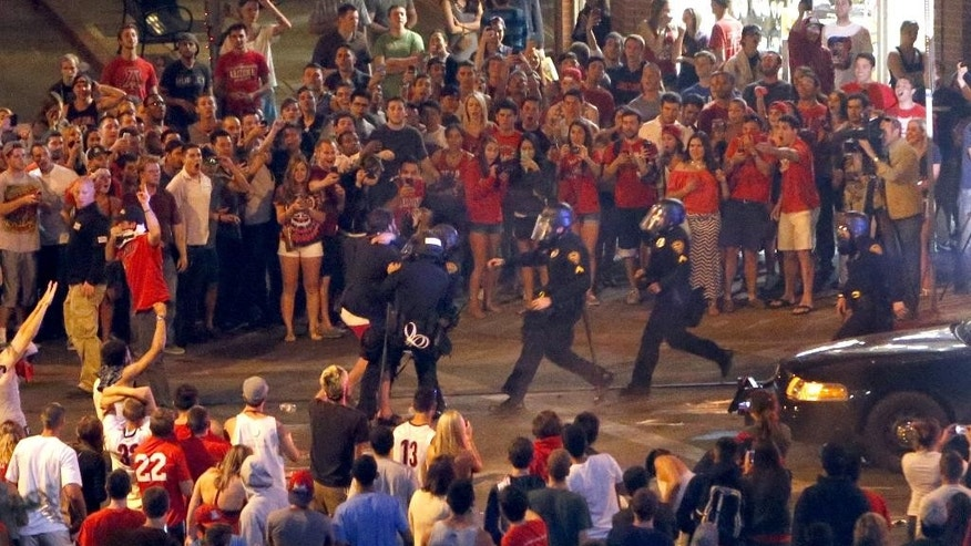 Tucson Police Officers rush out of their line to take a man into custody who had been taunting them and riling up a crowd of fans in Maingate Square, Saturday, March 29, 2014, in Tucson Ariz. following Arizona's loss to Wisconsin 64-63 in the West Region NCAA final. (AP Photo/Arizona Daily Star, Kelly Presnell)