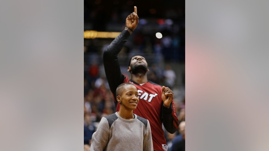 Miami Heat's LeBron James points skyward after the national anthem as Ebony Nettles-Bey stands with him before the Heat's NBA basketball game against the Milwaukee Bucks on Saturday, March 29, 2014, in Milwaukee. (AP Photo/Jeffrey Phelps)