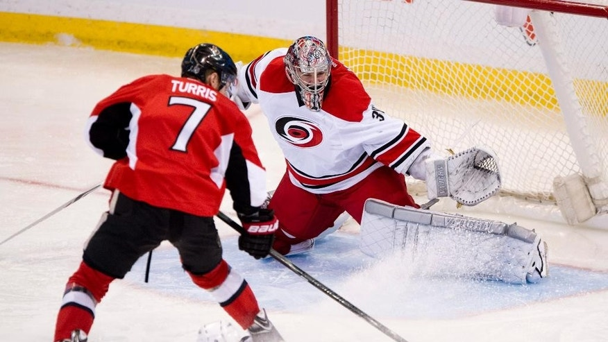 Carolina Hurricanes Andrei Loktionov slides along the ice behind Ottawa Senators Kyle Turris as he tries to score on goalie Cam Ward during second period NHL action Monday March 31, 2014 in Ottawa.  (AP Photo/The Canadian Press, Adrian Wyld)