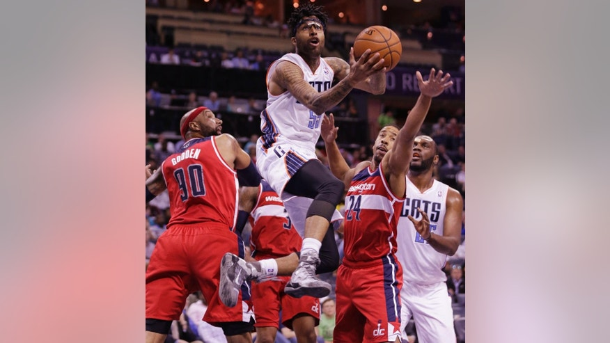 Charlotte Bobcats' Chris Douglas-Roberts (55) drives past Washington Wizards' Andre Miller (24) and Drew Gooden (90) during the first half of an NBA basketball game in Charlotte, N.C., Monday, March 31, 2014. (AP Photo/Chuck Burton)
