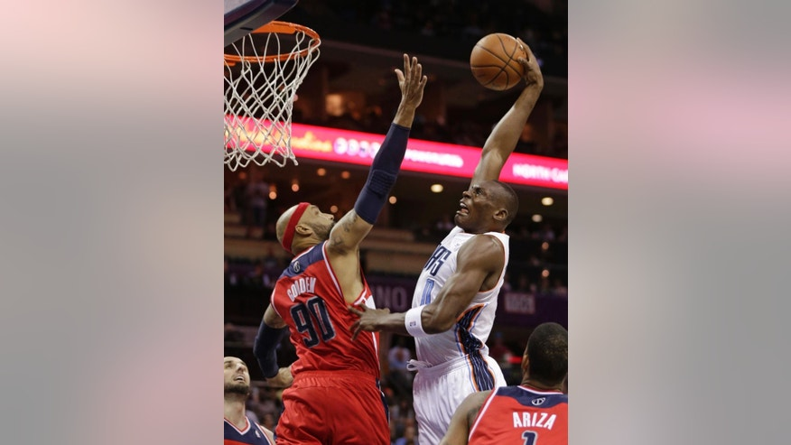 Charlotte Bobcats' Bismack Biyombo (0) goes up to dunk over Washington Wizards' Drew Gooden (90) during the first half of an NBA basketball game in Charlotte, N.C., Monday, March 31, 2014. (AP Photo/Chuck Burton)