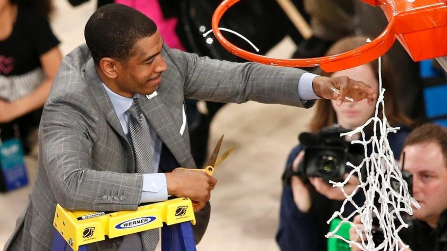 Connecticut head coach Kevin Ollie cuts the netting on the rim after his team defeating Michigan State 60-54 during a regional final at the NCAA college basketball tournament, Sunday, March 30, 2014, in New York. (AP Photo/Julio Cortez)