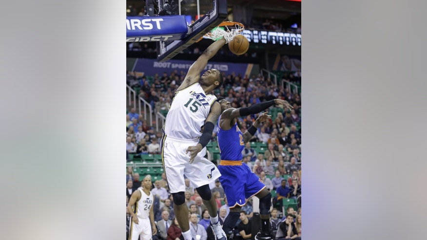 Utah Jazz's Derrick Favors (15) dunks the ball as New York Knicks' Iman Shumpert (21) defends in the first quarter during an NBA basketball game Monday, March 31, 2014, in Salt Lake City. (AP Photo/Rick Bowmer)