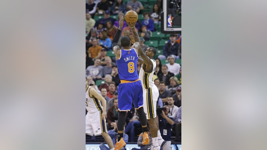 New York Knicks' J.R. Smith (8) shoots as Utah Jazz's Marvin Williams, rear, defends in the first quarter during an NBA basketball game Monday, March 31, 2014, in Salt Lake City. (AP Photo/Rick Bowmer)