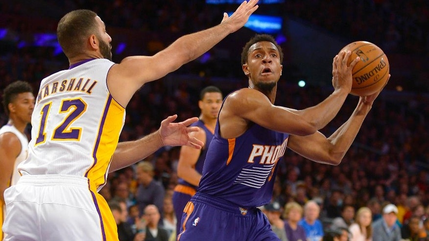 Los Angeles Lakers guard Kendall Marshall (12) guards Phoenix Suns guard Ish Smith (3) as he looks for the open in the first half of an NBA basketball game, Sunday, March 30, 2014, in Los Angeles.(AP Photo/Gus Ruelas)