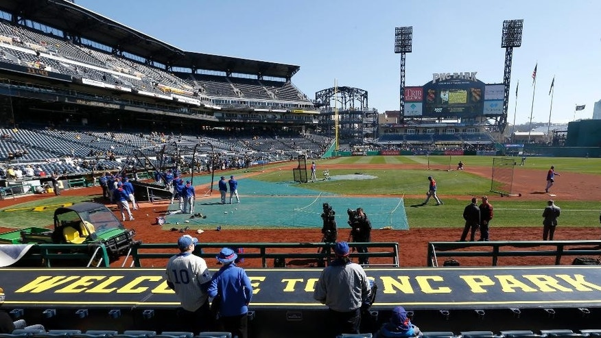 Chicago Cubs fans stand behind the first base dugout at PNC Park in Pittsburgh as their team takes batting practice before their opening day baseball game against the Pittsburgh Pirates on Monday, March 31, 2014, . (AP Photo/Keith Srakocic)