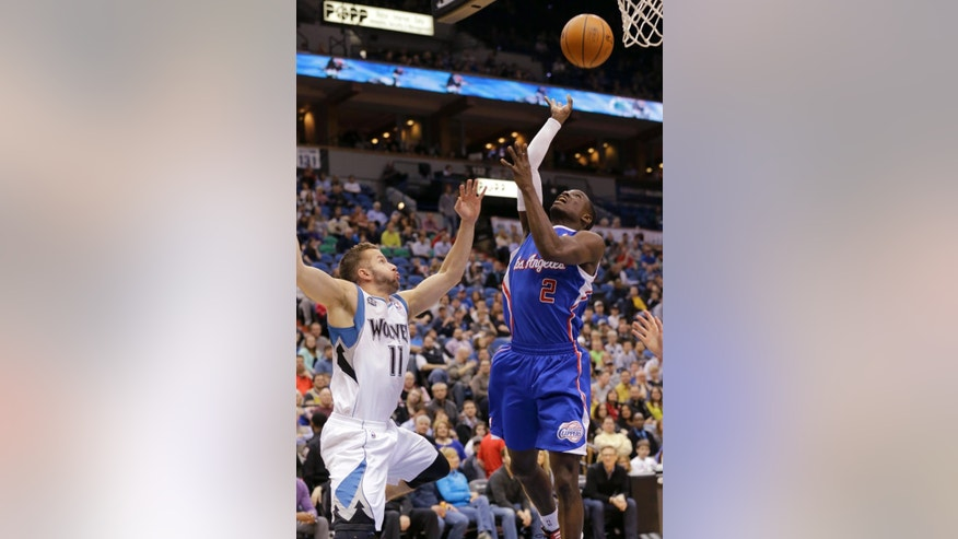 Los Angeles Clippers guard Darren Collison (2) goes up for a shot over Minnesota Timberwolves guard J.J. Barea (11), of Puerto Rico, during the second quarter of an NBA basketball game in Minneapolis, Monday, March 31, 2014.  (AP Photo/Ann Heisenfelt)