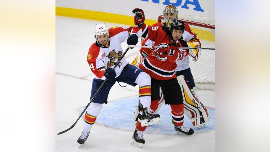 New Jersey Devils' Ryane Clowe, right, battles for position with Florida Panthers' Erik Gudbranson in front of Panthers goaltender Dan Ellis during the first period of an NHL hockey game Monday, March 31, 2014, in Newark, N.J. (AP Photo/Bill Kostroun)