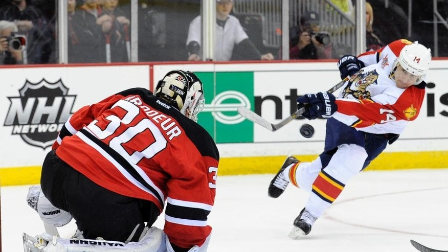 Florida Panthers' Tomas Fleischmann, right, of the Czech Republic, takes a shot against New Jersey Devils goaltender Martin Brodeur during the first period of an NHL hockey game Monday, March 31, 2014, in Newark, N.J. (AP Photo/Bill Kostroun)