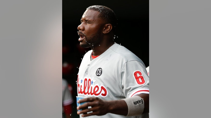 Philadelphia Phillies' Ryan Howard (6) splashes his face with a cup of water in the first inning of a baseball game against the Texas Rangers, Tuesday, April 1, 2014, in Arlington, Texas. (AP Photo/Tony Gutierrez)