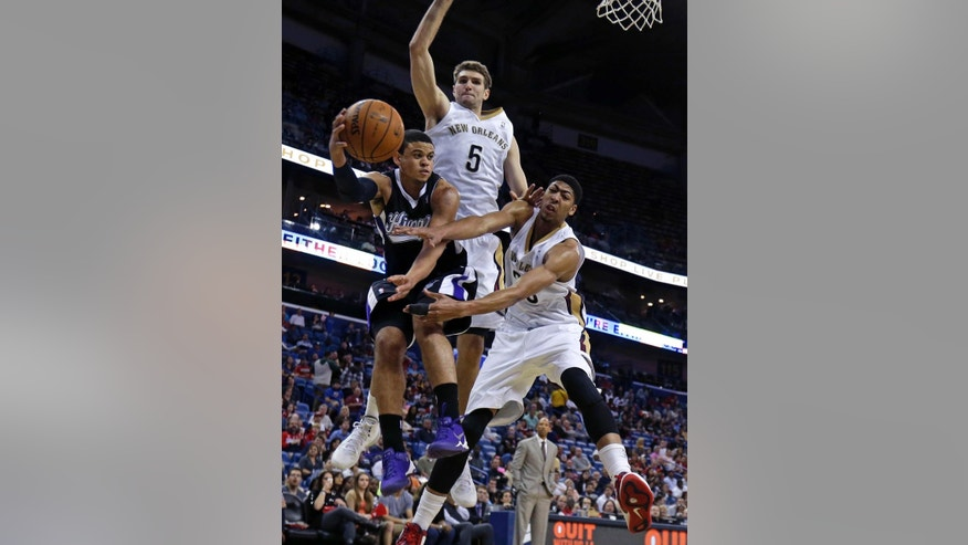 Sacramento Kings guard Ray McCallum passes around New Orleans Pelicans center Jeff Withey (5) and forward Anthony Davis (23) in the second half of an NBA basketball game in New Orleans, Monday, March 31, 2014. The Kings won 102-97. (AP Photo/Gerald Herbert)