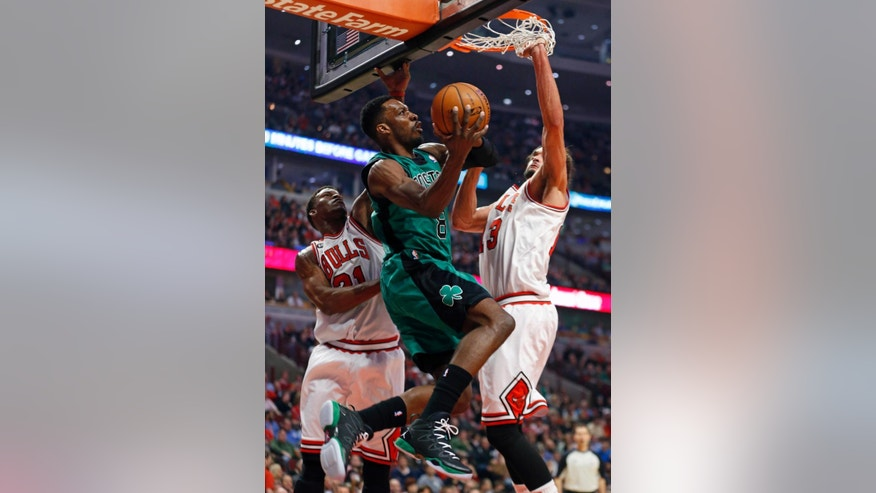 Boston Celtics forward Jeff Green, center, goes to the basket against Chicago Bulls guard Jimmy Butler, left, and center Joakim Noah, right, during the first half of an NBA basketball game in Chicago, Monday, March 31, 2014. (AP Photo/Kamil Krzaczynski)