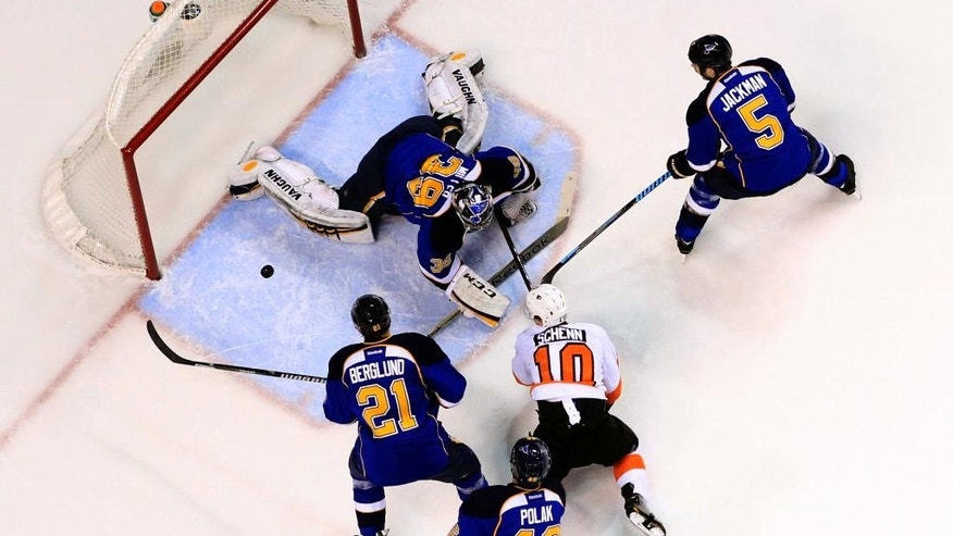 Philadelphia Flyers' Brayden Schenn (10) watches along with St. Louis Blues' Patrik Berglund (21), of Sweden, Roman Polak (46), of the Czech Republic, and Barret Jackman (5) as Blues goalie Ryan Miller (39) makes a save during the first period of an NHL hockey game Tuesday, April 1, 2014, in St. Louis. (AP Photo/Jeff Roberson)