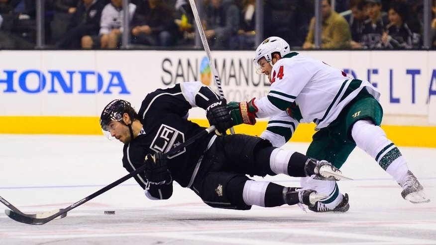 Los Angeles Kings defenseman Drew Doughty, left, stays on the puck as he battles Minnesota Wild left wing Matt Cooke (24) for it during the second period of an NHL hockey game, Monday, March 31, 2014, in Los Angeles. (AP Photo/Gus Ruelas)