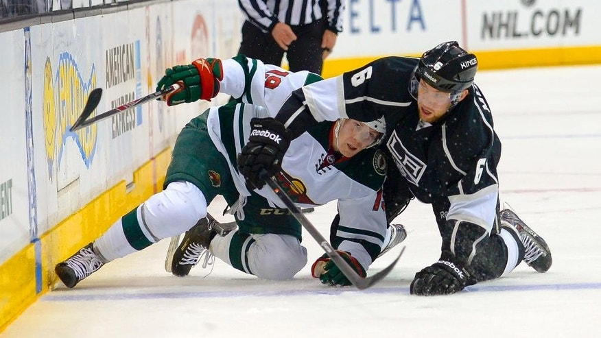 Minnesota Wild center Stephane Veilleux (19) and Los Angeles Kings defenseman Jake Muzzin (6) battle for the puck during the first period of an NHL hockey game, Monday, March 31, 2014, in Los Angeles. (AP Photo/Gus Ruelas)