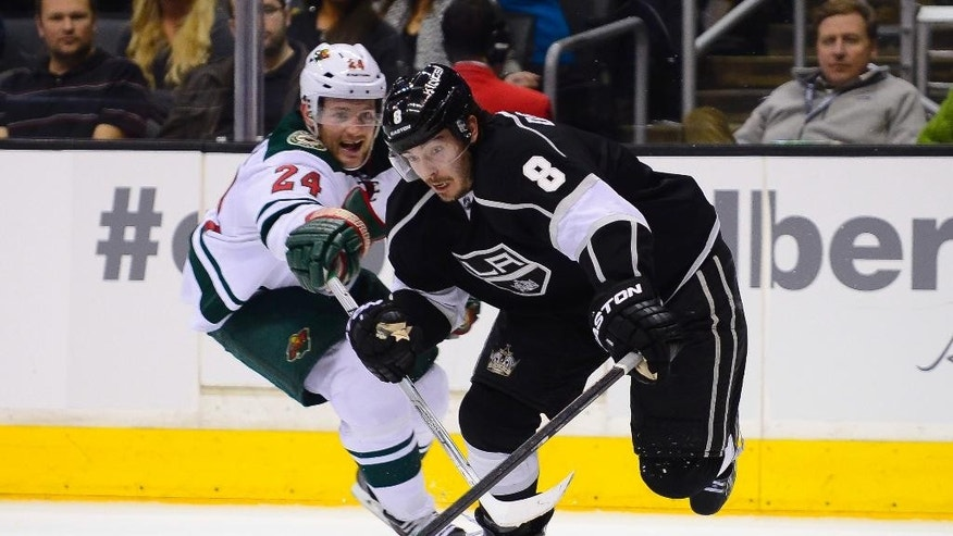 Minnesota Wild left wing Matt Cooke (24) reaches in as Los Angeles Kings defenseman Drew Doughty (8) keeps possession during the second period of an NHL hockey game, Monday, March 31, 2014, in Los Angeles. (AP Photo/Gus Ruelas)