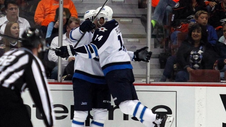 Winnipeg Jets right wing Anthony Peluso (14) leaps in celebration into left wing Eric Tangradi, left, after Tangradi scores in the second period of an NHL hockey game against the Anaheim Ducks Monday, March 31, 2014, in Anaheim, Calif. (AP Photo/Alex Gallardo)