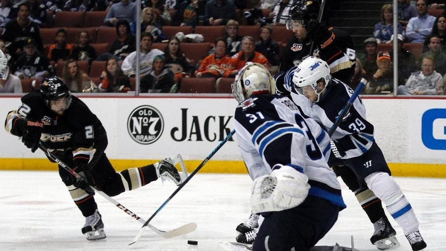 Anaheim Ducks center Mathieu Perreault (22) shoots the puck on Winnipeg Jets goalie Ondrej Pavelec (31), of the Czech Republic  and defenseman Tobias Enstrom (39) with Ducks left wing Patrick Maroon in the second period of an NHL hockey game Monday, March 31, 2014, in Anaheim, Calif. (AP Photo/Alex Gallardo)