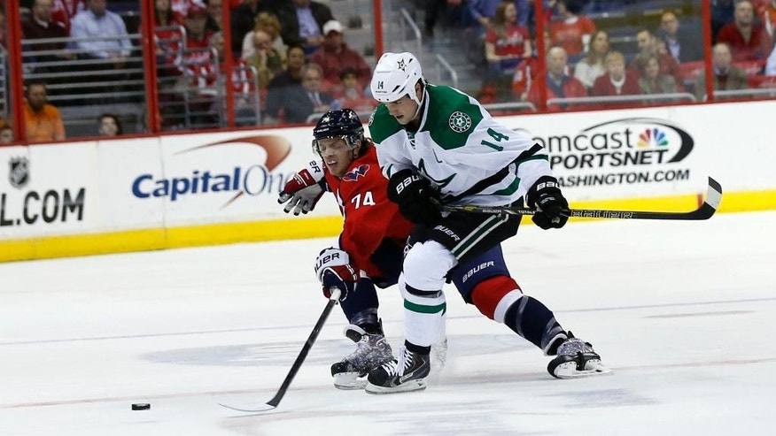 Washington Capitals defenseman John Carlson (74) reaches for the puck with Dallas Stars left wing Jamie Benn (14) in the first period of an NHL hockey game, Tuesday, April 1, 2014, in Washington. (AP Photo/Alex Brandon)